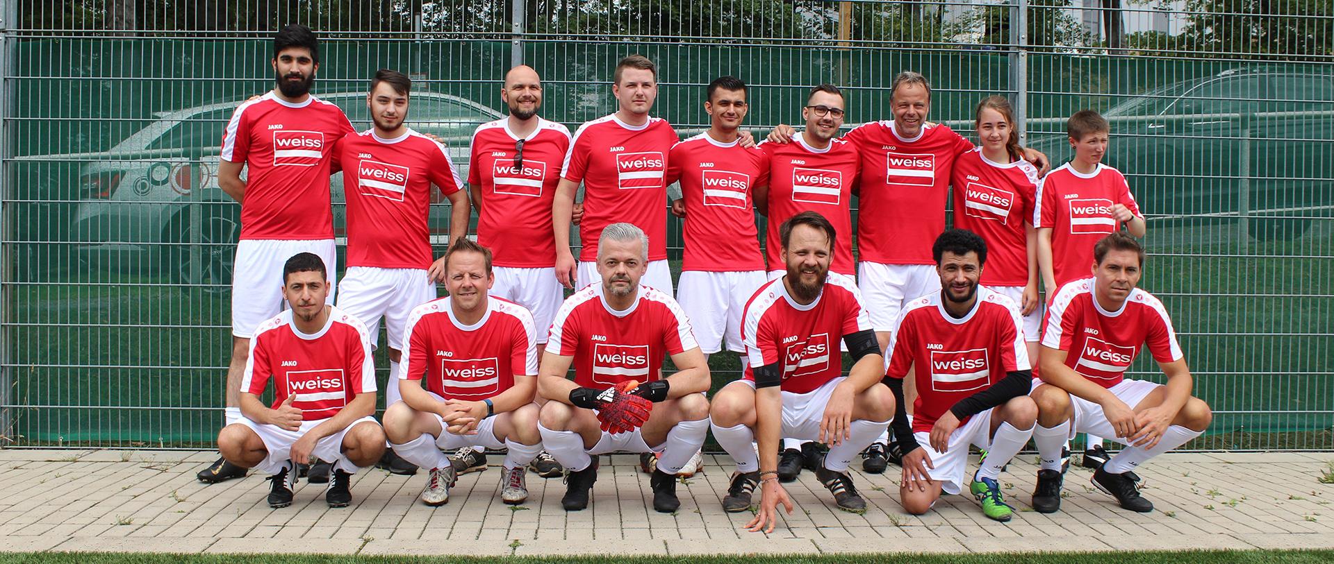Fußballmannschaft steht in roten Trikots vor Zaun