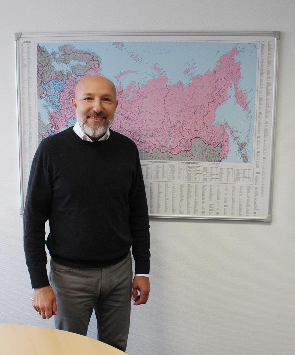 Rudolf Gerhardt, Exportmanager, steht vor Weltkarte | Erfahrungsbericht und Bewertung von Weiss